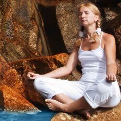 Woman Meditating On Rocks Near Waterfall