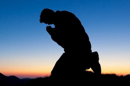 Shadow of Man Kneeling In Prayer During A Sunset